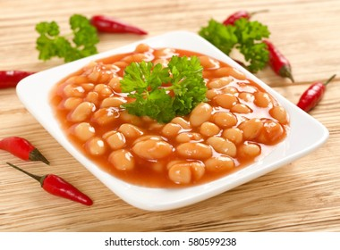 white beans in tomato sauce on wooden background