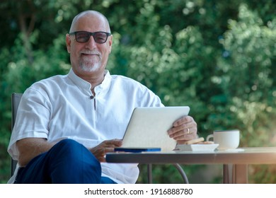 White bearded senior man working on tablet computer in the garden at home, looking and smile with camera