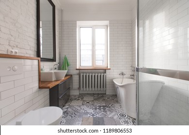 White beautiful attic bathroom in pastel gray and nude colours, with spectacular oval bath
