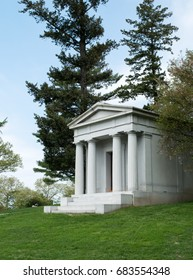 White beautiful mausoleum with tall columns, spring landscape