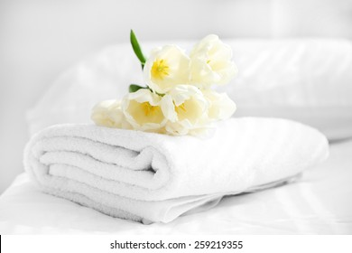 White beautiful tulips on fresh towels in hotel, close up