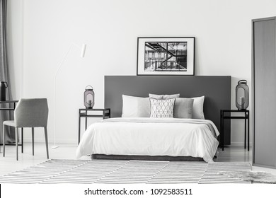 White bed between tables with lanterns in hotel bedroom interior with poster on grey bedhead