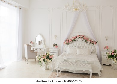 white bed. white bed in a classic style with a garland of leaves and flowers. the spring location. decorated in a spring decor. the white four-poster bed is decorated with flowers