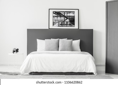 White bed with grey bedhead in minimal bedroom interior with poster and round table