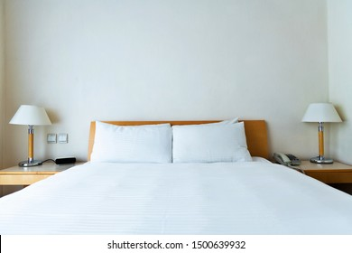 White bed sheet and pillows in hotel room.