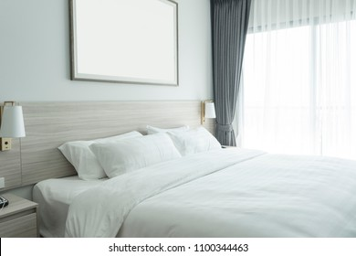 white bedding and pillow in hotel room, pillows on the bed with picture frame on wall.