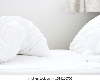 White bedding with sheet duvet and pillow in bedroom with curtain depicting someone just got up and left