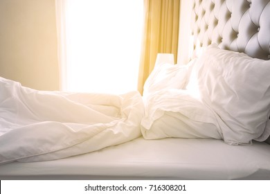 white bedding sheets and pillow.sunshine through window in the morning
