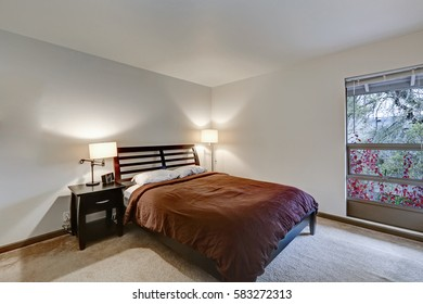 White bedroom in apartment building showcases wood bed with headboard and brown bedding illuminated by two lamps positioned side by side. Northwest, USA