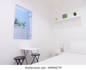 White bedroom with blue window frame, and plant pot outside, and white table and black chairs inside the room