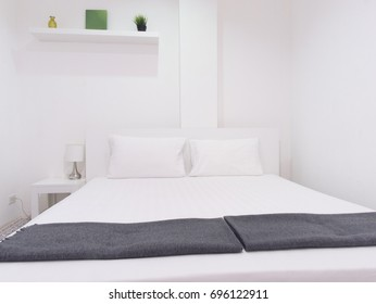White bedroom with green decoration objects on the shelf