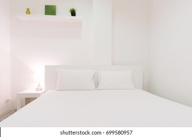 White bedroom with green decoration objects on the shelf and lamp opened