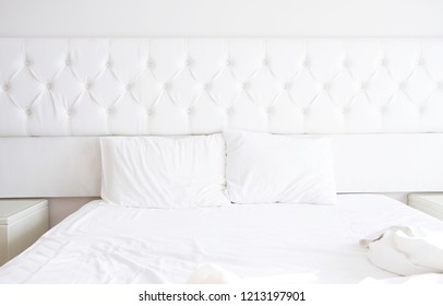 White bedroom interior design with bed and blank pillows. Bedding relax time. Copy space
