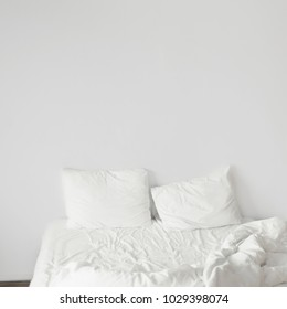 White bedroom with white pillows and white walls. Modern interior design
