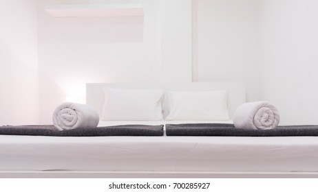 White bedroom with white towels, black blankets, and lamp