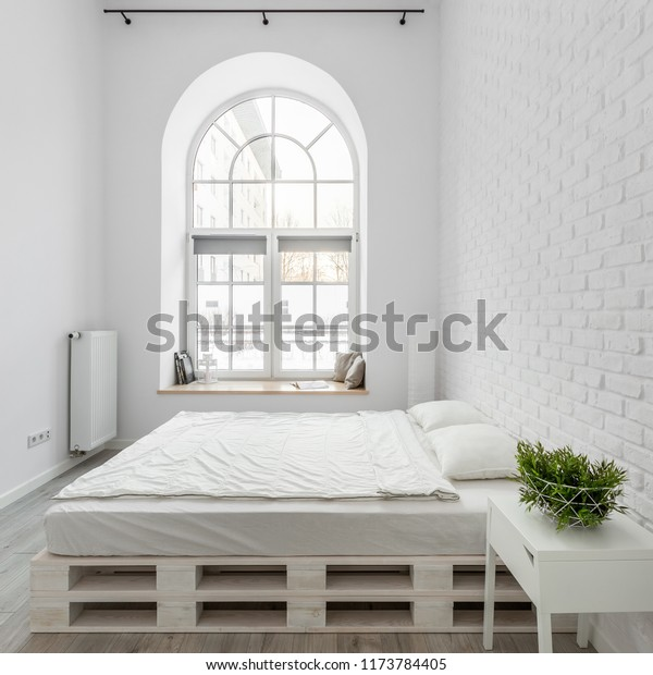 White bedroom with trendy pallet bed and brick wall