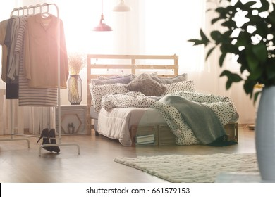 White bedroom with wooden bed, lamps, window and clothes rack