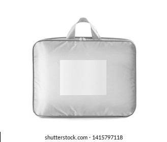 White bedspread, duvet or pillow in the retail bag isolated. Bedspread packed in to the PVC bag with empty label, front view against white background. Photo ready for mock up.