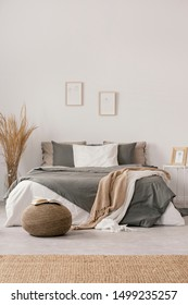 White and beige blankets on grey duvet on comfortable bed in bright bedroom interior