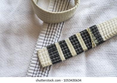 White belt of Brazilian Jiu-Jitsu with four degrees, on top of the kimono.