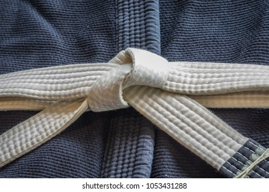 White belt of Brazilian Jiu-Jitsu with four degrees, tied in the kimono, knot of belt.