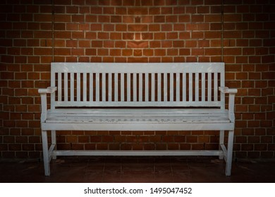 White bench in front of a brick wall