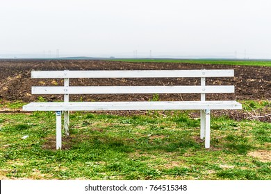 a white bench in the nature next to the field