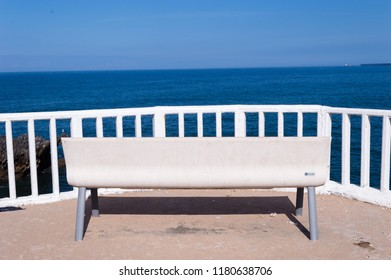 white bench overlooking the Cantabrian sea in the village of Candas, Asturias, Spain.