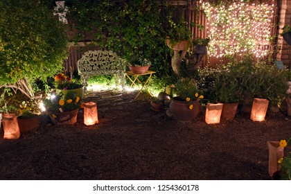 White bench in a southwest garden lit with traditional luminarias