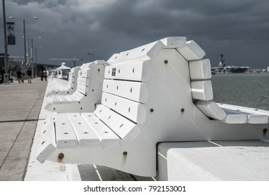 White benches along the boardwalk or sea wall of the Corpus Christi , Texas coastline bayfront. A downtown trip for travel and fun in the sun. A long deep perspective down the White Sea wall