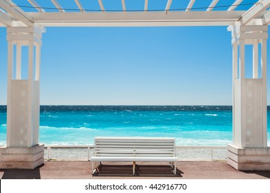 White benches on the Promenade des Anglais in Nice, France. Beautiful turquoise sea and beach