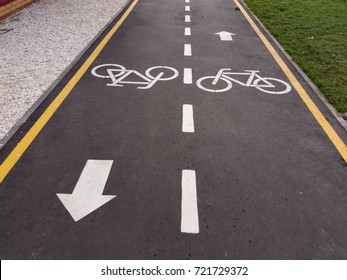 White bicycle sign with arrow on the asphalt, bike road sign on the street, bicycle lane sign on street, gray background