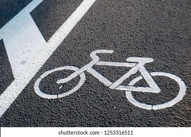 White bicycle sign on asphalt bike lane