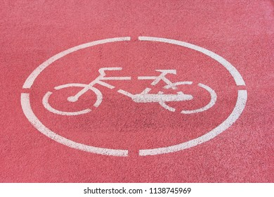 White bicycle sign on red bike path.