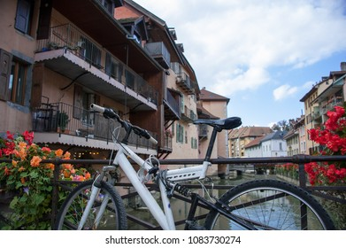 A white bicycle stands on a bridge over the river Thiou, Annecy old town. Picturesque scene with pastel coloured buildings in the background