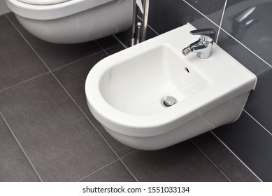 White bidet screwed to a gray tiled wall in the bathroom, close-up