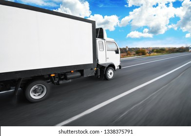 A white big box truck with space for text driving fast on the countryside road with trees and bushes against a blue sky with clouds