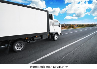 A white big box truck with space for text on the countryside road with trees and bushes against a blue sky with clouds