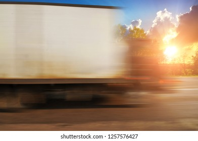 A white big boxed truck driving fast on the countryside road in motion with green trees and bushes against a sky with sunset