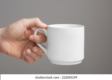 White big cup in a left hand./White big cup in a  hand.