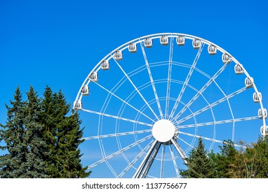 white big ferris wheel with cabins against the background of the blue sky in the park of attractions