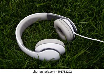 White big headphones on green grass