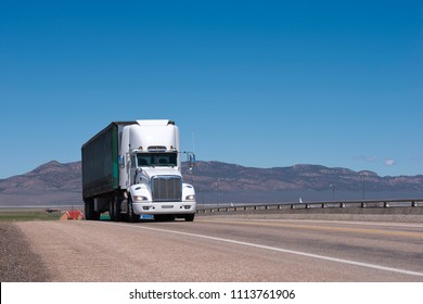 White big rig American long haul semi truck with tented semi trailer moving on wide divided turning highway with mountain on background for delivery of industrial cargo to warehouse and business