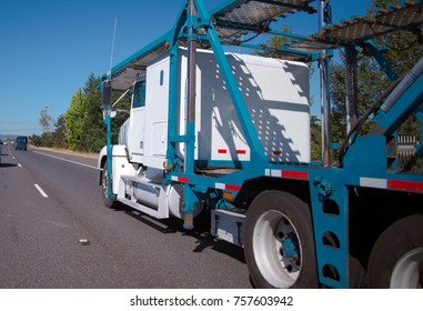 White Big rig American professional car hauler semi truck with two level trailer for transporting cars moving on multi-lines highway for pick up the cars for delivery