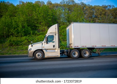 White Big rig day cab semi truck with roof spoiler for better aerodynamics and air resistance improvements transporting cargo in dry van semi trailer running on the road with green trees on the side