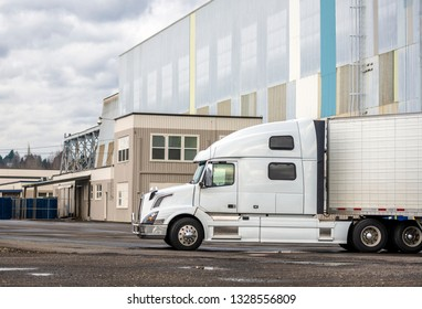 White big rig long haul semi truck with high cab and reefer semi trailer standing on parking lot waiting for loading and possibility of continuing to the destination according to approved schedule