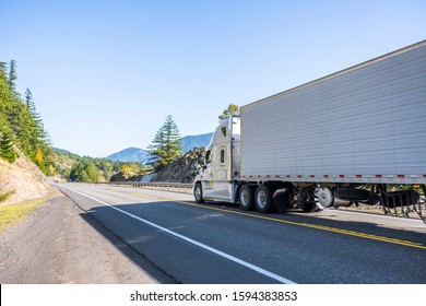 White Big rig powerful semi truck transporting frozen and chilled commercial cargo in refrigerator semi trailer running straight on the autumn mountain road with rock cliff and trees
