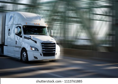 White big rig semi truck with chrome grille transporting goods in semi trailer driving on arched truss Interstate Columbia River draw bridge for delivery of commercial cargo to destination warehouse