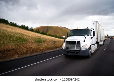 White big rig semi truck with dry van semi trailer driving in front of another traffic of semi trucks on the straight interstate highway with yellow hill roadside in California with stormy clouds