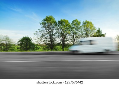 A white big van driving fast on the countryside road in motion with green trees and bushes against a blue sky, blur
